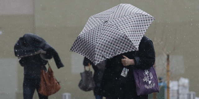 Women walk in the rain toward a federal court building in San Francisco, Monday, Feb. 25, 2019. A fierce winter storm packing winds in excess of 100 mph (160 kph) and predicted to bring as much as 8 feet (2.4 meters) of snow to the Sierra Nevada barreled into the West Coast on Monday, toppling trucks, triggering power outages and temporarily closing the major highway near Reno. (AP Photo/Jeff Chiu)