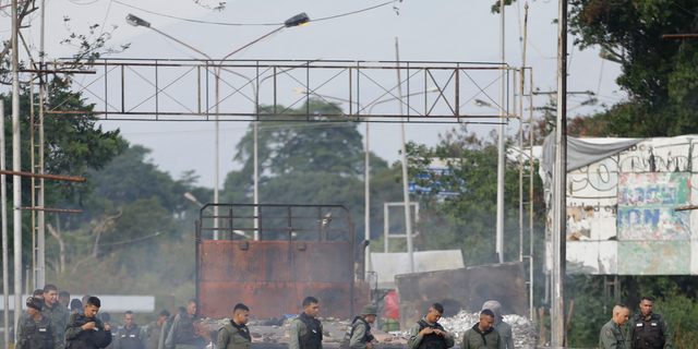 Venezuelan Bolivarian National Guard officers inspect trucks torched over the weekend during clashes with anti-government demonstrators trying to move aid across the Francisco de Paula Santander International Bridge in Urena, Venezuela, Tuesday, Feb. 26, 2019. Starting on Saturday, security forces on Venezuela's borders with Colombia and Brazil fired tear gas and buckshot on activists as they blocked emergency medical and food kits from crossing into Venezuela.