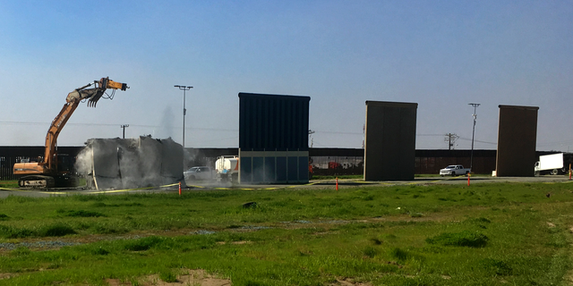 Work crews begin to demolish border wall prototypes in San Diego on Wednesday, Feb. 27, 2019. The Trump administration on Wednesday began to demolish eight prototypes of the president's prized border wall that the government built near San Diego one year ago. (AP Photo/Elliot Spagat)