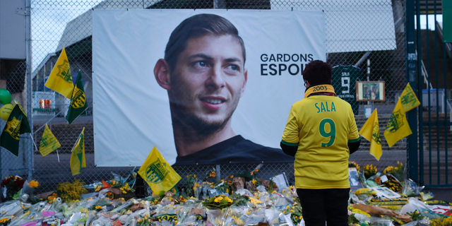 "FILE - In this Wednesday, Jan. 30, 2019, file photo, a Nantes soccer team supporters stops by a poster of Argentinian player Emiliano Sala and reading ""Let's keep hope"" outside La Beaujoire stadium before the French soccer League One match Nantes against Saint-Etienne, in Nantes, western France."