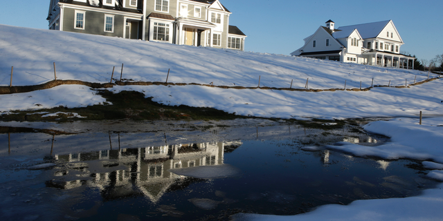 In this Thursday, Feb. 21, 2019 photo a recently constructed home, left, is reflected in water, in Natick, Mass. On Tuesday, Feb. 26, the Commerce Department reports on U.S. home construction in December. (AP Photo/Steven Senne)