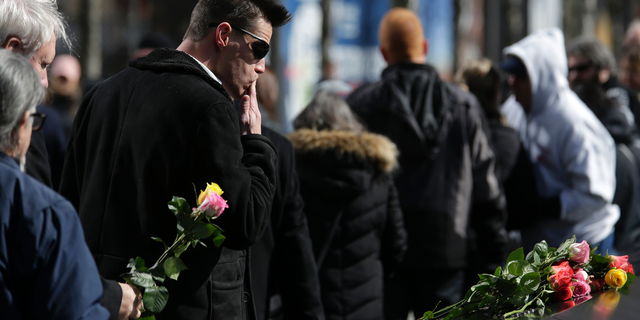 People place flowers over the names of the victims of the 1993 World Trade Center bombing during a ceremony at the 9/11 Memorial in New York, Tuesday, Feb. 26, 2019. (AP Photo/Seth Wenig)