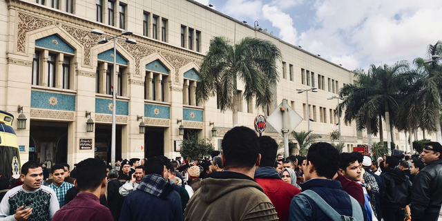 People gather outside Ramsis train station in Cairo, Egypt, Wednesday, Feb. 27, 2019. An Egyptian medical official says 20 people have been killed and dozens injured when a major fire erupted at the main train station in Cairo. Mohammed Said, the head of the Cairo Railroad hospital, says the death toll is expected to rise further following the blaze on Wednesday. (AP Photo/Nariman El-Mofty)