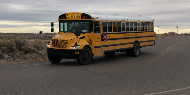 A school bus evacuates students from Sue V. Cleveland High School in Rio Rancho, New Mexico, on Thursday, Feb. 14, 2019, after a shot was fired on the campus. Police and school officials said no one was injured and a suspect was taken into custody. (AP/Russell Contreras)