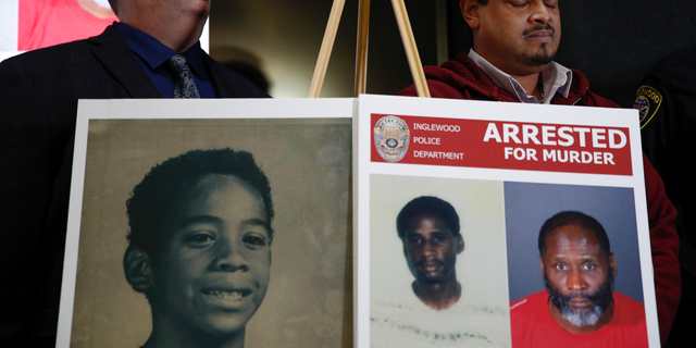 Hubert Tillett, right, brother of William Tillett, stands behind a display showing his brother, bottom left, during a news conference Wednesday, Feb. 20, 2019, in Inglewood, Calif. Authorities say a 50-year-old man is in custody in connection with the kidnapping and killing of then 11-year-old William Tillett in Southern California nearly three decades ago. (AP Photo/Jae C. Hong)