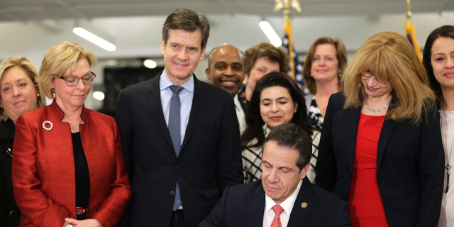 New York Gov. Andrew Cuomo, center, signs the Child Victims Act in New York, Thursday, Feb. 14, 2019. Cuomo has signed into law long-sought legislation that extends the statute of limitations so sexual abuse victims can have more time to seek criminal charges or file lawsuits. (AP Photo/Seth Wenig)