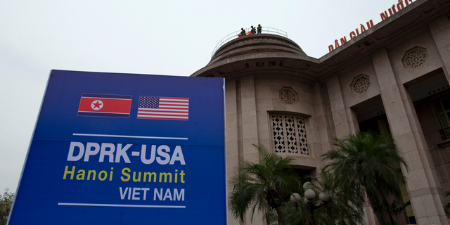 Vietnamese soldiers watch from a top of a building neighboring Government Guesthouse and the Metropole hotel next to a poster featuring upcoming summit between the U.S. and North Korea in Hanoi, Vietnam, Sunday, Feb. 24, 2019. The second summit between U.S President Donald Trump and North Korean leader Kim Jong Un will take place in Hanoi on Feb. 27 and 28. (AP Photo/Gemunu Amarasinghe)