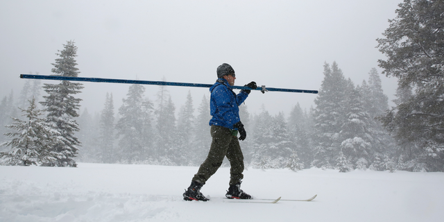 Snow falls as John King of the Department of Water Resources, crosses a meadow while conducting the third manual snow survey of the season at the Phillips Station near Echo Summit, Calif., Thursday, Feb. 28, 2019. The survey found the snowpack at 113 inches deep with a snow water equivalent of 43.5 inches at this location at this time of year. (AP Photo/Rich Pedroncelli)