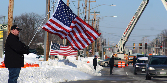 Timothy Nelson holds an American flag in front of Oak Creek Assembly of God Church in Oak Creek, Wis., showing support for the first responders on the day of Officer Matthew Rittner's funeral, Wednesday, Feb. 13, 2019. Rittner was killed in the line of duty Feb. 6. It is the sixth first-responder funeral that Nelson, who works at a senior care facility, has attended in the past 12 months. (Adam Rogan/The Journal Times via AP)