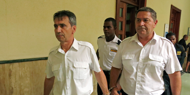 FILE - In this June 17, 2014 file photo, French pilots Bruno Odos, left, and Pascal Jean Fauret, who have been formally charged with drug trafficking, are escorted to a courtroom in Santo Domingo, Dominican Republic. Nine men go on trial in southern France for an alleged cocaine trafficking between the Caribbean and Europe, including two pilots who escaped the Dominican Republic to avoid 20-year prison sentences. (AP Photo/Ezequiel Abiu Lopez, File)