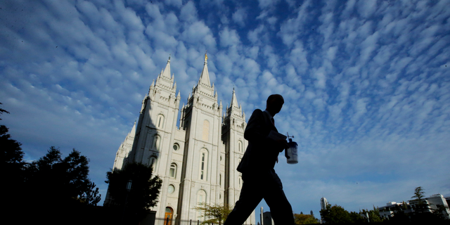 FILE - In this Sept. 14, 2016, file photo, a man walks past the Salt Lake Temple, a temple of The Church of Jesus Christ of Latter-day Saints, at Temple Square in Salt Lake City. Parents of Mormon missionaries will be able to hear their children's voices a lot more often under new rules announced Friday, Feb. 15, 2019, that allow the proselytizing youngsters to call home every week instead of only twice a year. (AP Photo/Rick Bowmer, File)