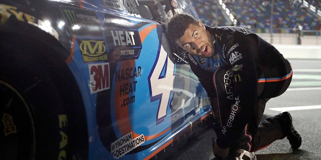 Darrell Wallace Jr. adjusts his driving shoes before getting into his car before the first of two qualifying auto races for the NASCAR Daytona 500 at Daytona International Speedway, Thursday, in Daytona Beach, Fla. (AP Photo/John Raoux)