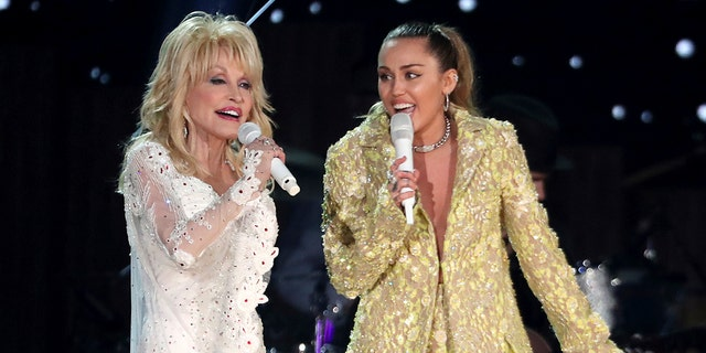 Dolly Parton, left, with her goddaughter Miley Cyrus, performing