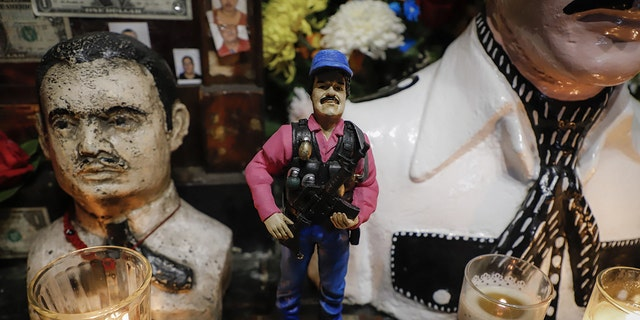 """A statue of Mexican drug lord Joaquin """"El Chapo"""" Guzman, is displayed for sale near a bust of narco-saint Jesus Malverde, at his chapel in Culiacan, Sinaloa state in northwest Mexico, on February, 19, 2019"""