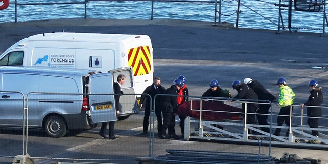 A stretcher carrying a body is removed from the Geo Ocean III specialist search vessel docked in Portland, England, Thursday Feb. 7, 2019.