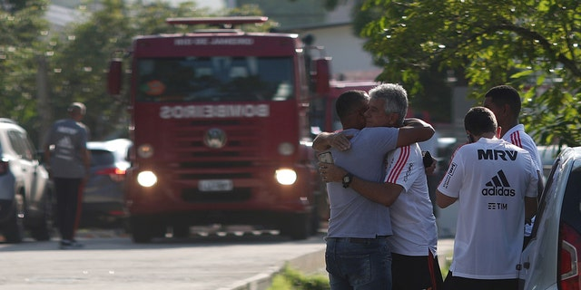 People wait for information in front of the training center of Rio's soccer club Flamengo, after a deadly fire