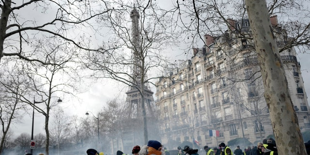 Yellow western protesters run away from tear gas fired by riot police as they hold pressure on French President Emmanuel Macron's government for the 13th straight weekend of demonstration in Paris, France, Saturday, February 9, 2019.