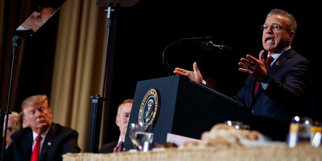 President Donald Trump listens as Gary Haugen, Chief Executive Officer and Founder of International Justice Mission, speaks during the National Prayer Breakfast, Thursday, Feb. 7, 2019, in Washington. (AP Photo/ Evan Vucci)