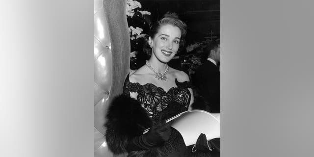Circa 1950: A portrait of American actor Julie Adams wearing a strapless evening gown, pearls, and long gloves while holding a menu in a restaurant.
