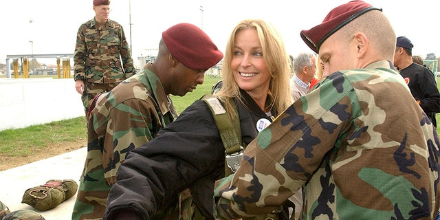 Actress Bo Derek (C) getting suited up in a parachute harness to jump from a US Army Parachute practice tower while on the USO Holiday Tour.