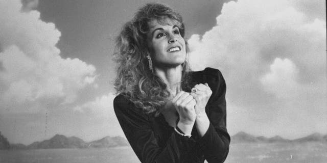 """Actress Jodi Benson posing in front of an ocean scene backdrop as the voice of the mermaid Ariel for the movie """"The Little Mermaid. """""""