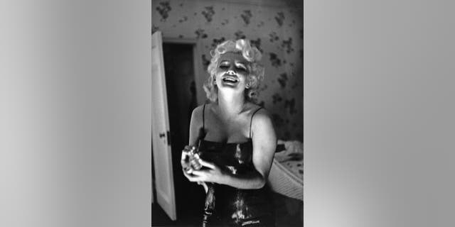 "Actress Marilyn Monroe gets ready to go see the play ""Cat On A Hot Tin Roof"" playfully applying her makeup and Chanel No. 5 Perfume on March 24, 1955 at the Ambassador Hotel in New York City."