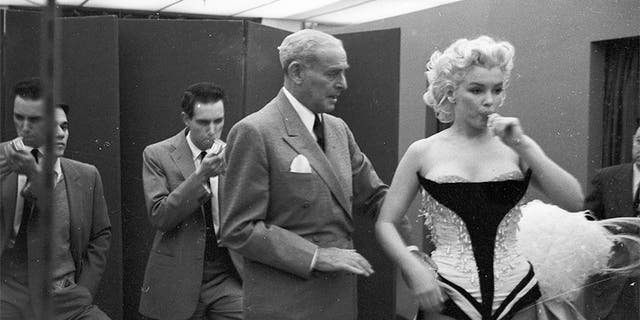 NEW YORK - MARCH 1955: Movie star Marilyn Monroe gets fitted for her costume in a dressing room before riding a pink elephant in Madison Square Garden for a circus charity event in March 1955 in New York City, New York.