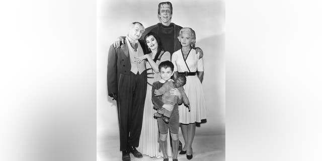 """Members of the Munster family in a publicity still for Season 1 of the comedy-horror TV series """"The Munsters,"""" 1964. Left to right: Al Lewis (1923 - 2006) as Grandpa, Yvonne De Carlo as Lily Munster, Butch Patrick as Eddie Munster, Fred Gwynne as Herman Munster and Beverley Owen as Marilyn Munster."""