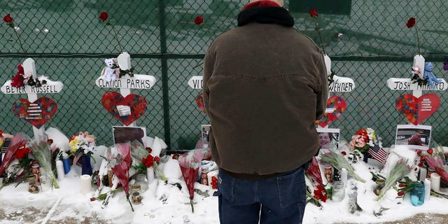 A man prays at a makeshift memorial Sunday, Feb. 17, 2019, in Aurora, Ill., near Henry Pratt Co. manufacturing company where several were killed on Friday. (AP Photo/Nam Y. Huh)