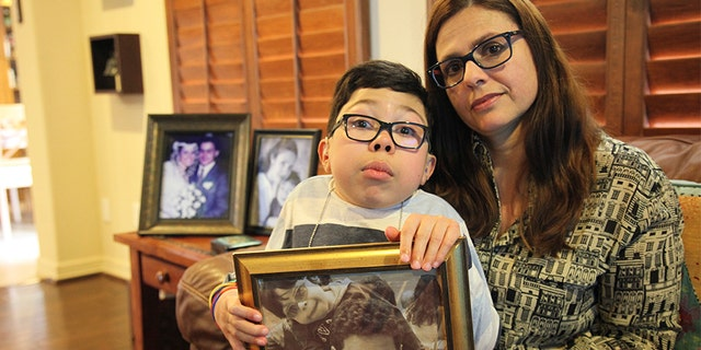 Sergio Cardenas holds a picture of himself with his father Gustavo as he sits on the lap of his mother Maria Elena Cardena, Gustavo's wife, at their home in Katy, Texas, Friday, Feb. 15, 2019. Gustavo, a Citgo executive, has been held in detention by the Venezuelan government along with five other Citgo employees since November of 2017, but their preliminary hearing has been postponed 12 times, leaving the families to question whether their loved ones are being held as pawns in a high-stakes political negotiation.