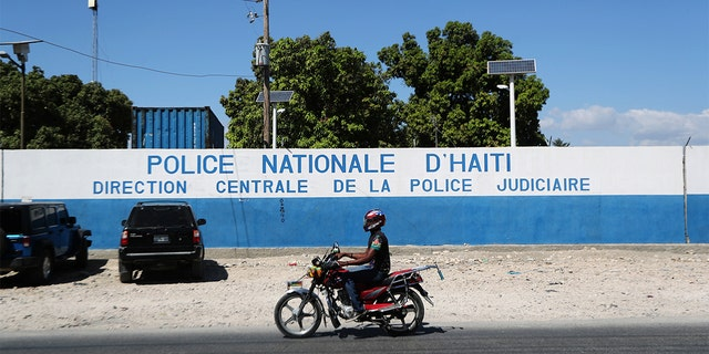 A man rides a bike in front of a main Haitian police station, where according to local media, a group of foreign nationals including Americans were detained, after anti-government protests, in Port-au-Prince, Haiti. (Ivan Alvarado / REUTERS)