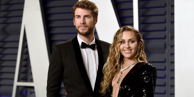 Liam Hemsworth, left, and Miley Cyrus arrive at the Vanity Fair Oscar Party.