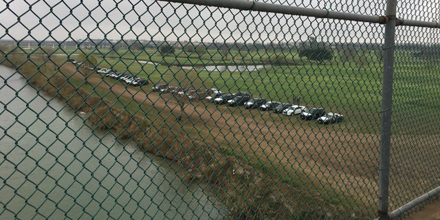 Looking down at Eagle Pass Texas where US law enforcement has lined the riverbank.
