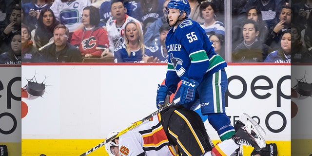 Calgary Flames' James Neal, bottom, holds his mouth after taking a high stick to the face from Vancouver Canucks' Alex Biega (55) and losing teeth during the third period of an NHL hockey game Saturday, Feb. 9, 2019, in Vancouver, British Columbia. (Darryl Dyck/The Canadian Press via AP)