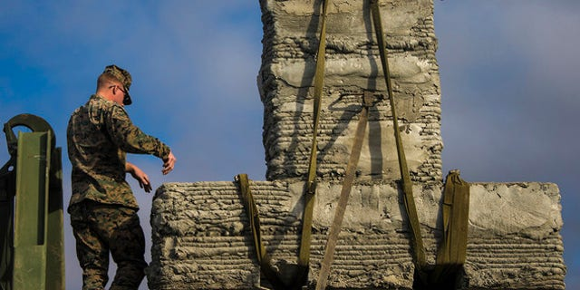 Marines with 7th Engineer Support Battalion, 1st Marine Logistics Group, work to secure a concrete bridge support column during the concrete printing exercise at Camp Pendleton, Calif., Dec. 12, 2018.