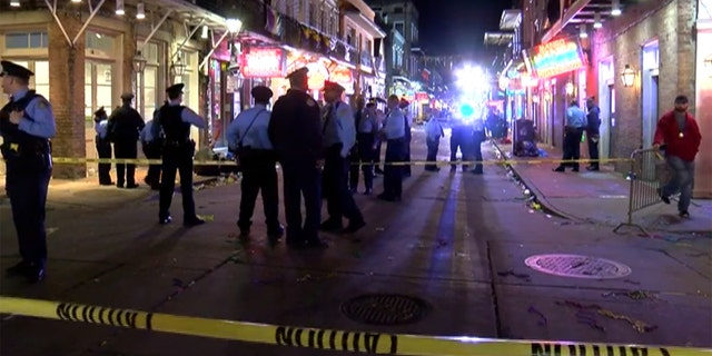 A woman was killed and a security guard was injured after a man stole the guard's gun and opened fire on Bourbon Street in New Orleans early Sunday, officials said.