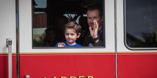 Owen Coulter, 5, and his dad, Darin, who is a firefighter ride home in a firetruck after he made a miraculous 56-day recovery at Dell Children's Hospital in Austin, Texas.