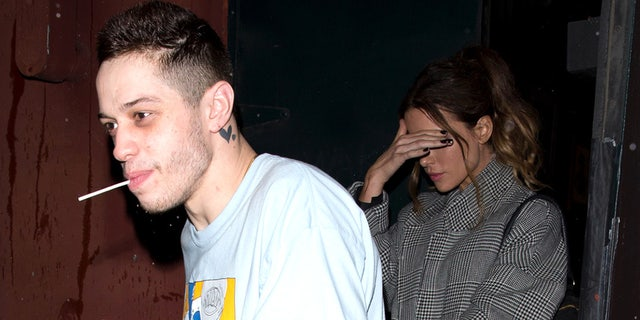 Kate Beckinsale, right, shields her face from cameras as rumored boyfriend Pete Davidson leads her out of Largo at the Coronet Comedy Club on Feb. 1, 2019, in Los Angeles, Calif.