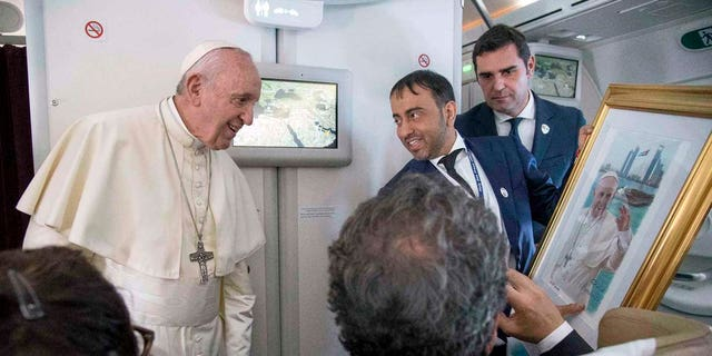 Pope Francis receives a gift from a journalist during his flight from Abu Dhabi to Rome, Tuesday, Feb. 5, 2019. Pope Francis has concluded his historic visit to the Arabian Peninsula with the first-ever papal Mass in the birthplace of Islam. (Luca Zennaro/Pool Photo via AP)