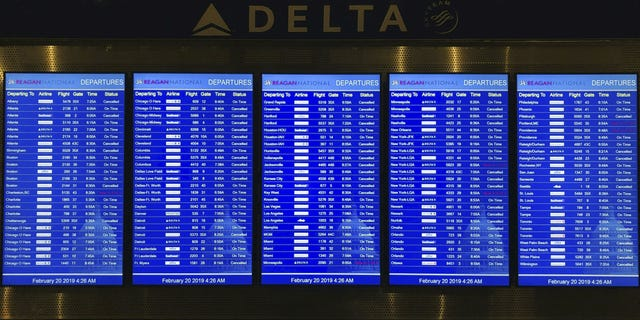The flight status of dozens of scheduled flights leaving from Ronald Reagan Washington National Airport in Washington D.C. is seen on Feb, 20, 2019.