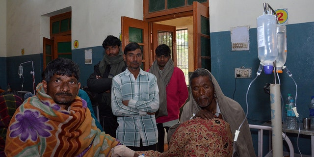 Two men who consumed bootleg alcohol, sit on a hospital bed as relatives look on, in Saharanpur, northern state of Uttar Pradesh, India February 11, 2019. REUTERS/Stringer - RC1A90540A20