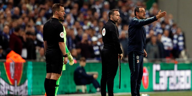 Chelsea's manager Maurizio Sarri, right, remonstrates with Kepa while substitute keeper Willy Caballero, obscured, waits to be subbed on. (AP Photo/Alastair Grant)