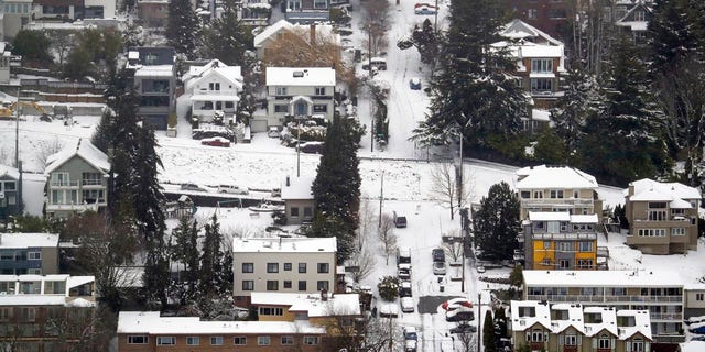Streets, homes and cars remain snow-covered on one of Seattle's steeper hills, Queen Anne, Monday, Feb. 11, 2019. Schools and universities closed across Washington state and the Legislature canceled all hearings as the Northwest dealt with snow and ice and prepared for more as a series of winter storms socked the region. (AP Photo/Elaine Thompson)