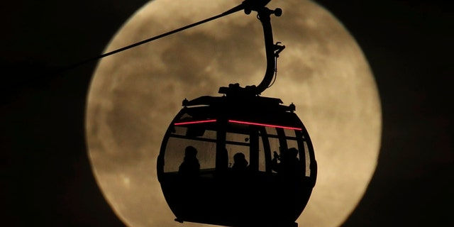 File photo - An Emirates Air Line cable car is silhouetted against the backdrop of the 'supermoon' in Greenwich, London, Tuesday, Feb. 19, 2019.