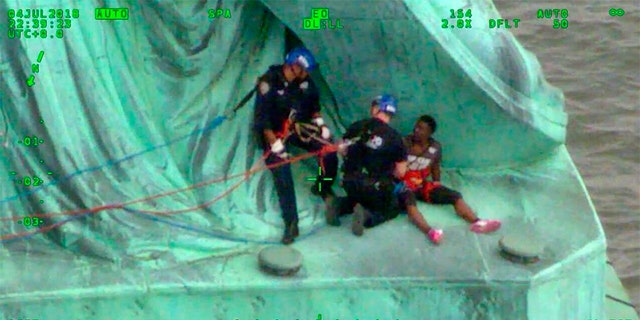 In this July 4, 2018, frame from video provided by the New York City Police Department, members of the NYPD Emergency Service Unit work to safely remove Therese Okoumou, a protester who climbed onto the Statue of Liberty and was charged with misdemeanor trespassing and disorderly conduct. (NYPD via AP)