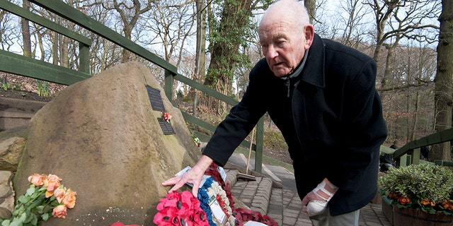 Tony Foulds tends to a memorial honouring 10 U.S. airmen who died in a plane crash in Endcliffe Park, Sheffield, England, Wednesday, Feb. 13, 2019. Foulds was just a kid running around in the park on Feb. 22, 1944 when a U.S. Air Force crew decided to crash and die rather than take the chance of hitting them. He's dreamed of honoring them for decades.