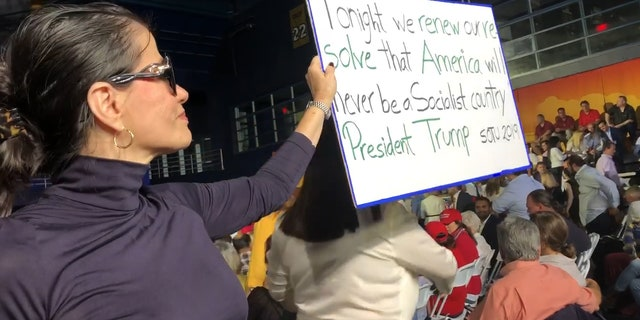Venezuelan holds up sign at Trump's speech in Miami: