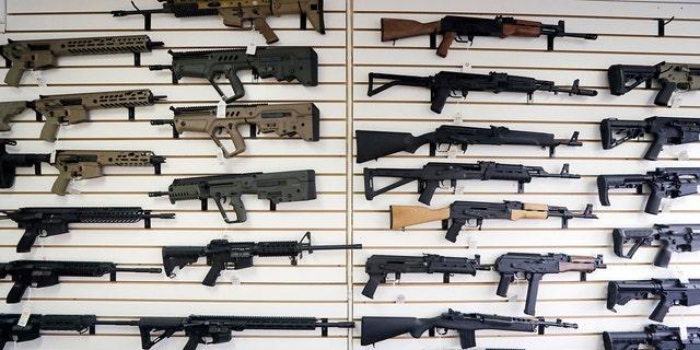 Semi-automatic rifles fill a wall at a gun shop in Lynnwood, Wash. (AP Photo/Elaine Thompson, File)