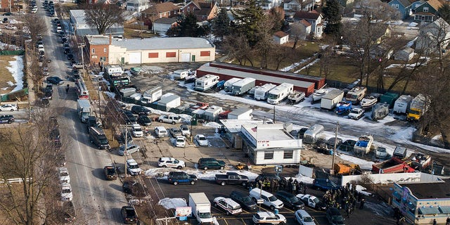 Law enforcement personnel gather near the scene of a shooting at an industrial park in Aurora Ill. on Friday Feb. 15 2019