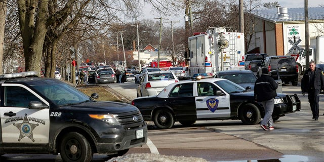 Law enforcement personnel gather near the scene of a shooting at an industrial park in Aurora, Ill., on Friday, Feb. 15, 2019.